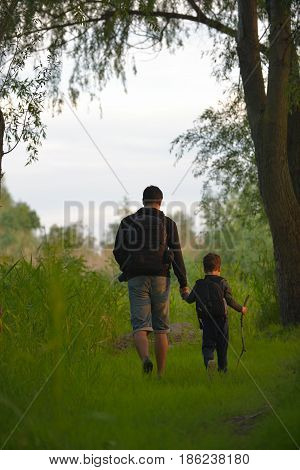 Father and son walking into the forrest at sunset
