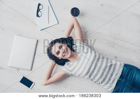 Top View Of Girl Resting On The Floor And Smiling. She Is Happy, Her Hands Are Behind The Head, She