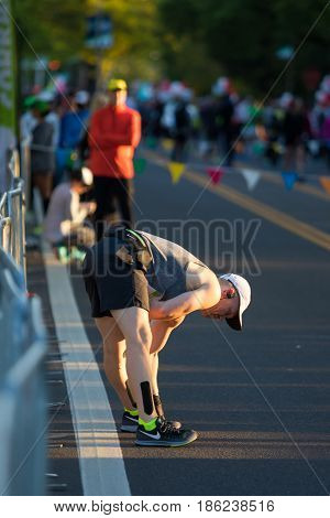 EUGENE, OR - MAY 7, 2017: Runner stretches before the start of the 2017 Eugene Marathon race held on the University of Oregon campus.