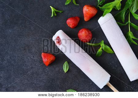 Eskimo - ice cream with strawberries and birch juice on a black concrete background