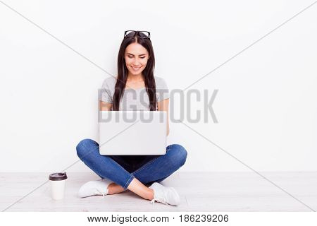 Smiling Teen In Casualwear Is Sitting With Crossed Legs On The Floor At Home. She Is Doing Online Sh