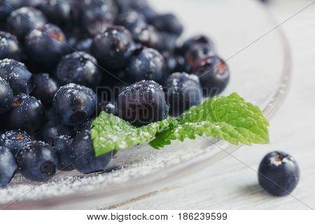 Fresh bilberry on a glass plate. Healthy breakfast.