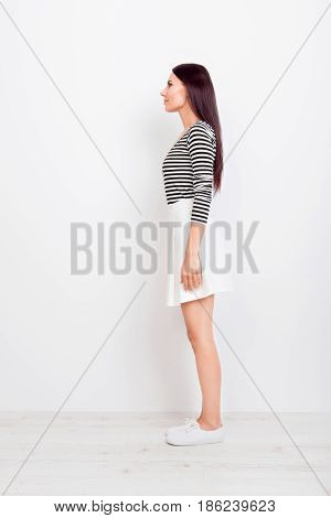 Full Size Profile View Of Brunette Girl In Casual Clothes And White Shoes On Pure White Background