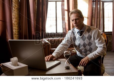 Portrait of psychiatrist man working in his in office. Psychiatrist man using laptop computer and looking at camera. Psychology concept.