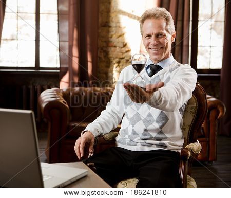 Portrait of handsome psychiatrist man smiling and looking at camera. Psychiatrist man holding and representing hourglass in hand while waiting for patients in his office.