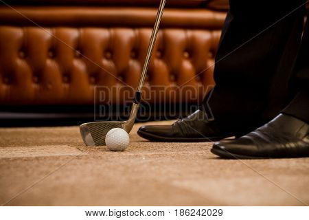 Man playing golf at office alone. Sport for recovering your nerves after hard working day or week. Golf at office concept.