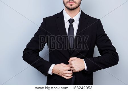 Close Up Photo Of Serious Confident Man In Formal Black Suit And Tie Buttoning Jacket