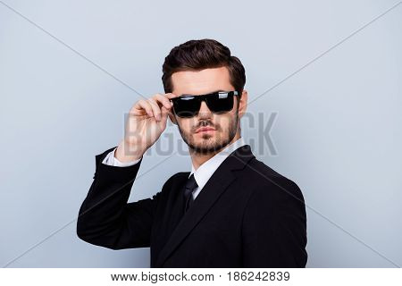 Portrait Of Handsome Young Serious Man In Black Siut And Glasses Trying  To Remain Anonymous