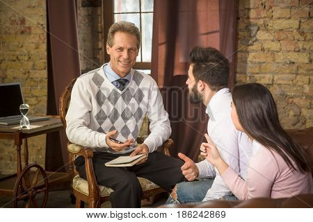 Young man and woman telling about their family problems to handsome middle aged psychologist. Psychology man communicating with young couple at psychologist's office.