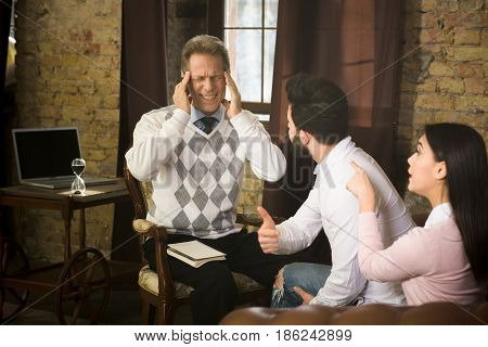 Couple screaming and shouting at psychologist's office. Psychologist man touching his head and trying to concentrate on their existing problems.