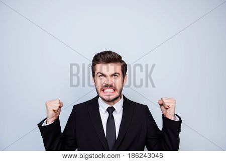 Young Very Angry Man In Black Suit Showing Fists And Looking Up On Copyspace Over His Head In Rage
