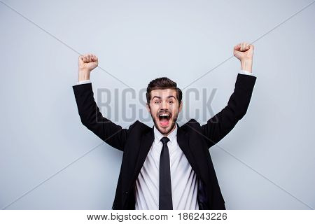 Happy Excited Man Triumphing With Raised Fists On Gray Background