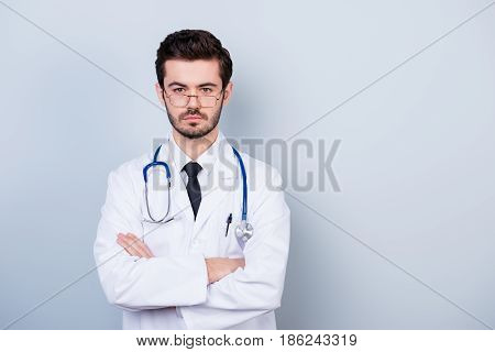 Portrait Of Concentrated Minded Doctor In White Coat Standing With Crossed Hands Against Gray Backgr