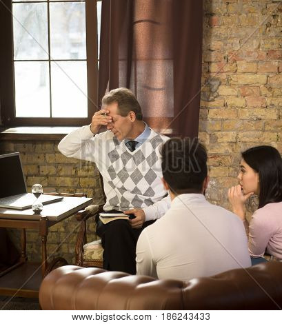 Psychology concept. Psychologist does not want to provide professional assistance to his patients. Young couple listening to psychologist and thinking about their life at psychologist's office.