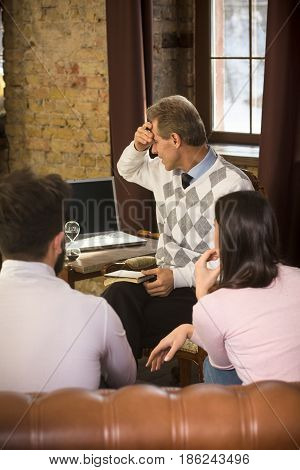 Psychologist does not want to provide professional assistance to his patients. Young couple listening to psychologist and thinking about their life at psychologist's office. Psychology concept.