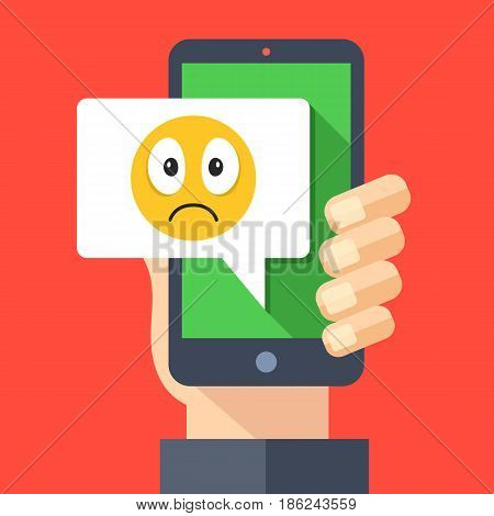 Hand holding smartphone with sad emoji message on screen. Sad emoticon icon. Social networking, instant messaging on mobile device, online chat concepts. Modern flat design vector illustration