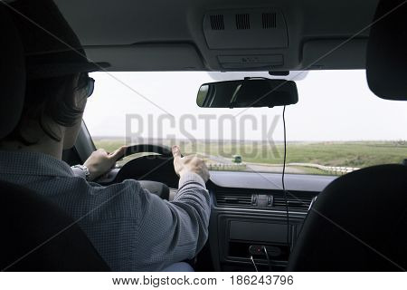 video recorder driving a car on highway. hidden camera. The man in the hat drives the car.