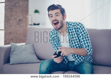 Young Happy Excited Man Sitting On Sofa Holding Joypad And Playing Video Games And Having Fun