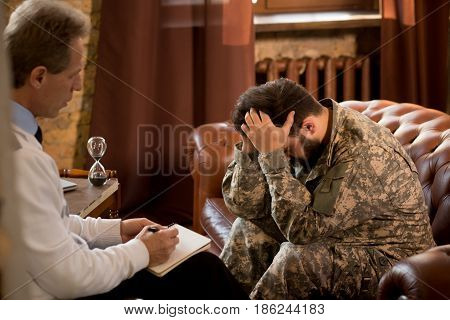 Military man communicating with psychologist. Psychologist providing moral assistance to soldier who has been in hot spots. Military psychologist.