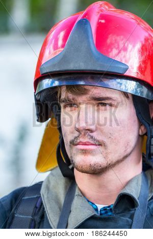 Portrait of a fireman with car on background