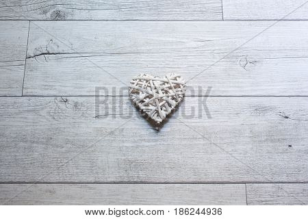 Heart made with white branches on the wooden background