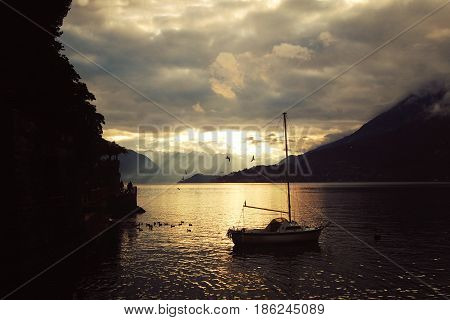 Silver linings in Lake Como at the sunset. Yacht. Boat on the water. Sunset view. Lombardy. Varenna Italy.