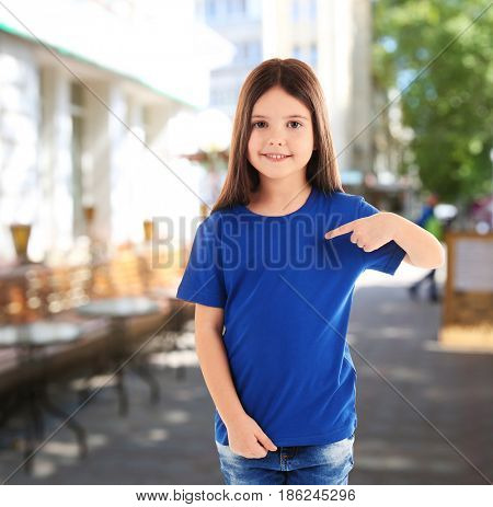 Little girl in stylish t-shirt on city street