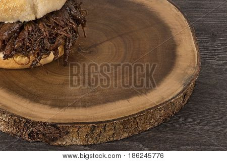 Close up on pulled pork sandwich isolated on wooden plank.