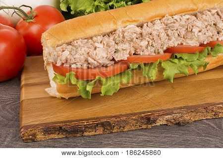 Close up on submarine tuna sandwich vegetables in background.