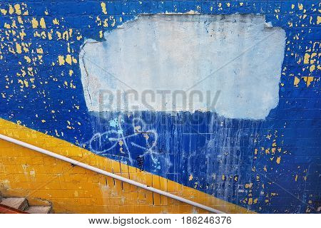 The wall of the underground passage decorated in the colors of the Ukrainian national flag round metal railing in the middle an empty place of white cement for the text.