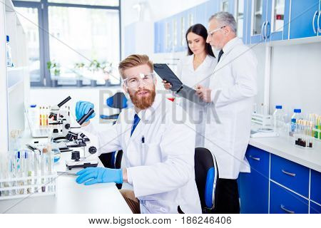 Portrait Of Young Handsome Bearded Stylish Intern, Who Is Wearing Gloves And Labcoat, Safety Glasses