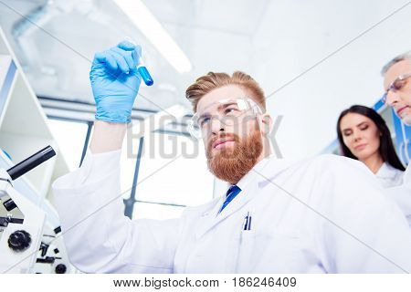Close Up Portrait Of Young Handsome Red  Bearded Stylish Focused Researcher, Who Is Looking At The B