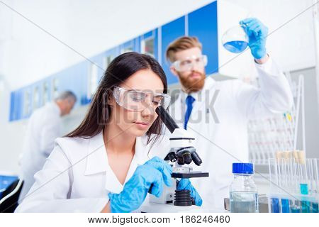 Team Work. Young Lab Worker In Safety Glasses Is Analysing The Sample In The Microscope. She Is In A