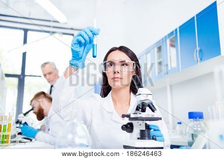 Young Brunette Cute Lab Worker In Safety Glasses Is Analysing The Sample In The Lab Tube. She Is In