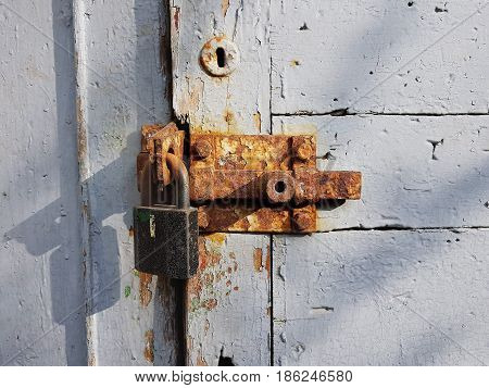 The old wooden door painted in white paint with a round keyhole at the top and an iron rusty heck with a large lock the evening sun casts a shadow on the left side of the door.