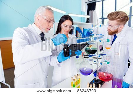 Team Work. Three Scientists Are Working Together  For New Experiment In The Lab, All Wearing Labcoat