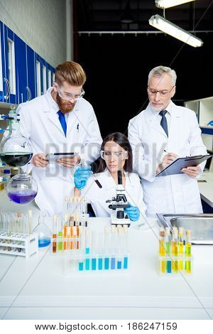 Team Work Of Three. Group Of Scientists Are Working For Invent Together, All Are Wearing Labcoats An