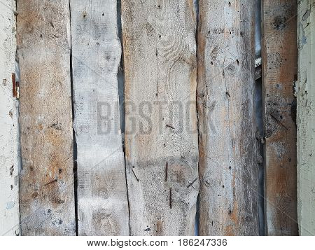 Rough unplaned natural wooden planks tender brown color rusty big nails hammered into them designer background texture modern with empty space for text.