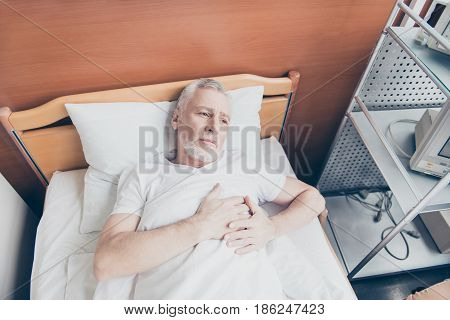 Aged patient is lying in the bed and holding his hands near to heart. He feels lonely and sad he dreams to be healthy