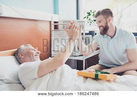 Give Me Five! Young Stylish Red Bearded Guy Is Visiting And Cheering Up His Grandpa Lying In Bed At