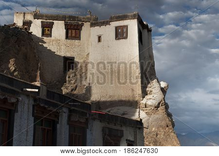 Traditional Tibetan house on the rock: high white wall at the top of the window with wooden frame terrace against a blue sky background with clouds and mountains Leh Ladakh India.