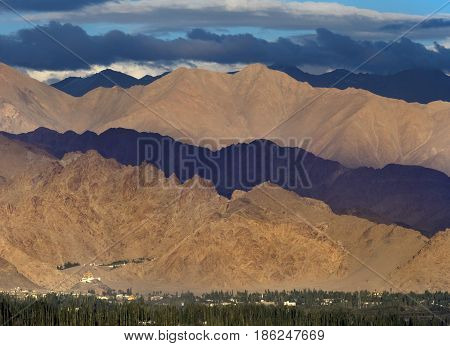Cloudy weather in the mountains: storm clouds cast shadows on the arrays part of the hills are lit by the sun part is dark at the foot of the mountains there is a village with green trees India.