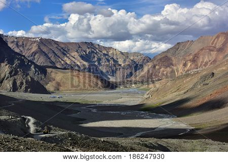 Panoramic view of the high mountains of the valley: huge mountain ranges in the foreground a shadow from the mountains the road passes in the blue sky cumulus white clouds the Himalayas India.