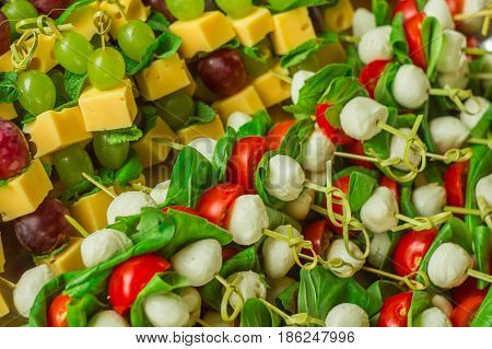 appetizer canape cheese with white and red grapes and tomato on bamboo skewers