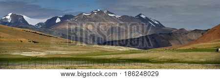 High mountain valleys: in the foreground there is a green highland pasture in the background there are huge peaks the peaks are covered with glaciers a sunny summer day a trip through the Himalayas India.