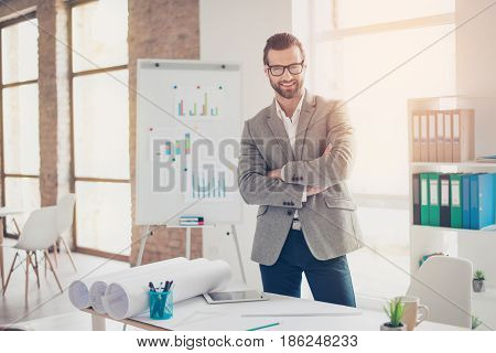 Confident Smiling Architect In Formal Wear And Glasses Standing With Crossed Hands At The Table With