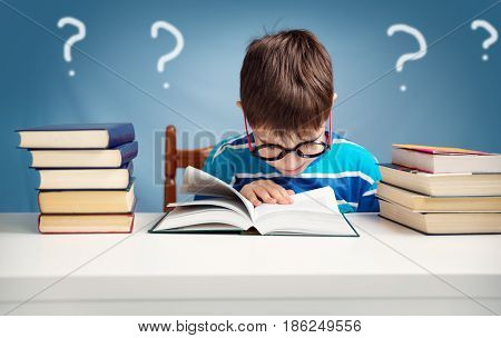 seven years old child reading a book at home. Boy studing at table on blue background