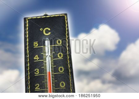 Leather thermometer with blue sky clouds and lens flare