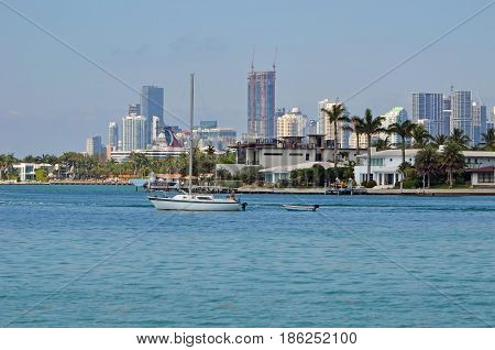 Sailboat under engine power cruising past Delido Island ion the Florida Intra-coastal waterway with Miami skyline in the distance.