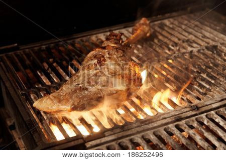 Lamb leg being fried on charcoal grill